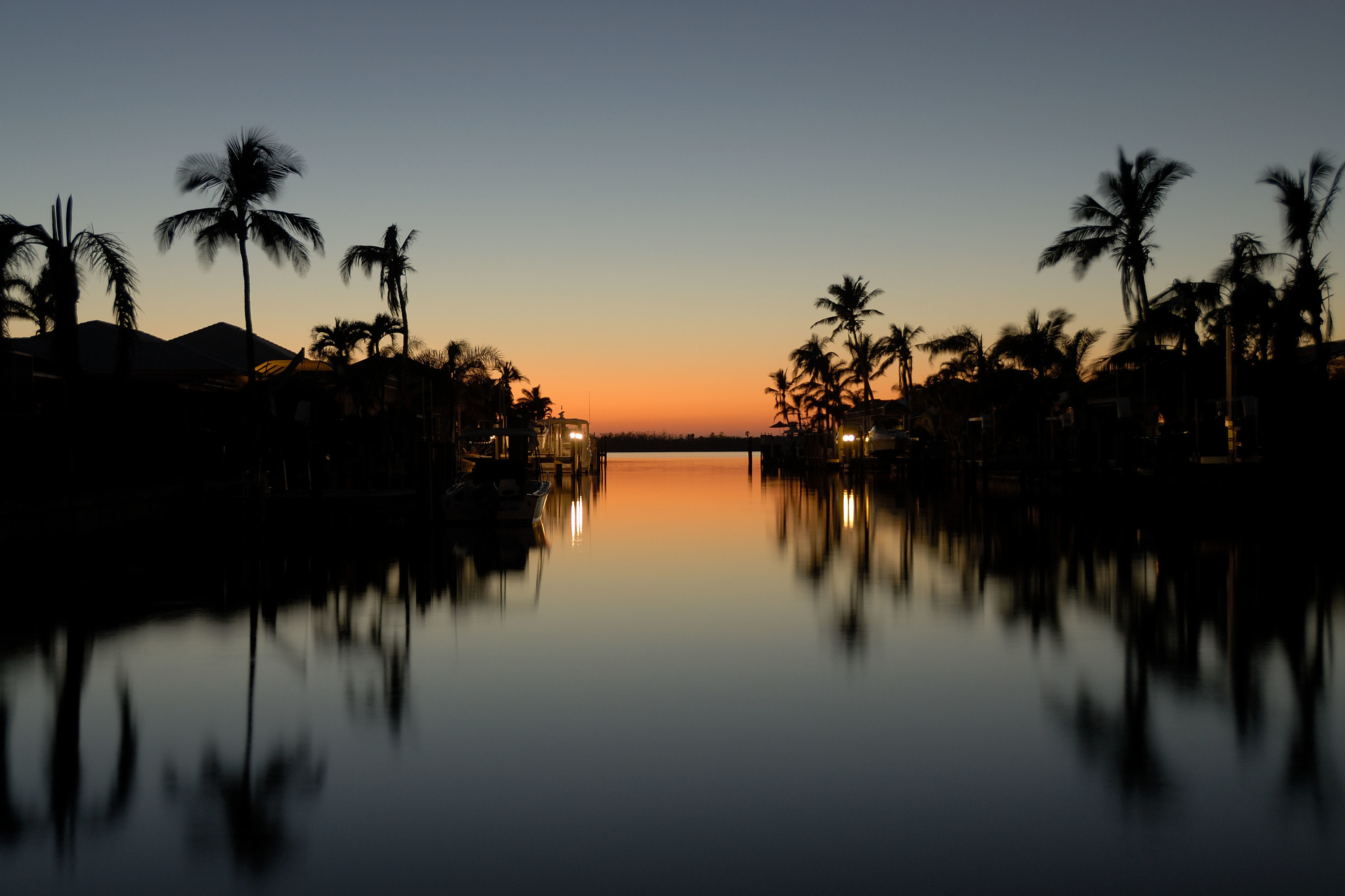 a sunset over the still water with palm trees in the shadows