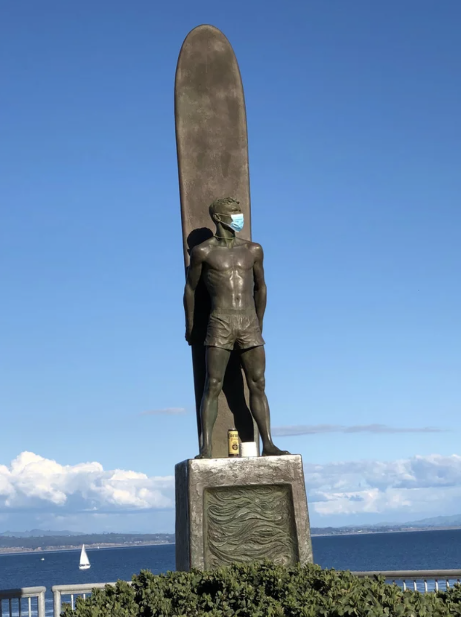 A mask has been put on a statue of a surfer