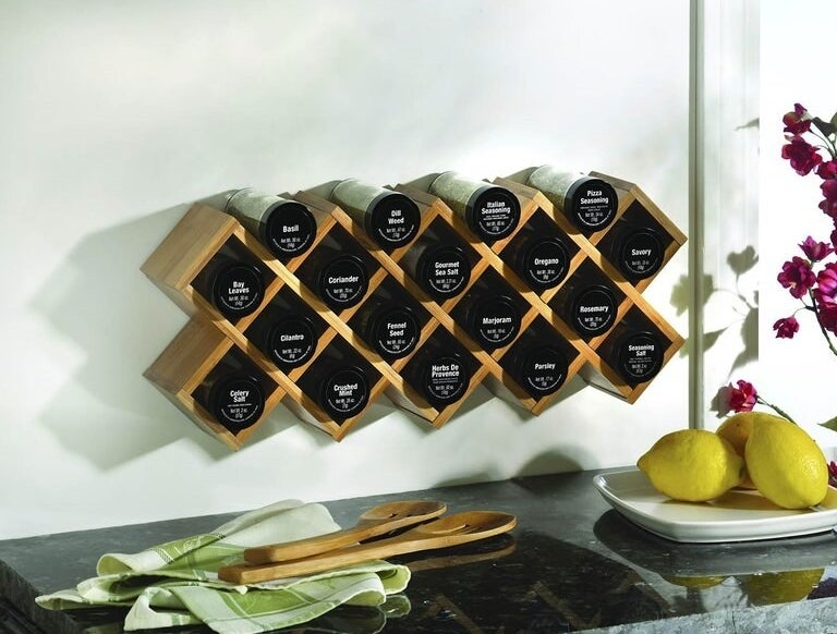 A criss cross wooden spice rack with 18 labeled jars