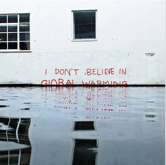 """I don't believe in global warming"" is written on a wall with rising water around it"