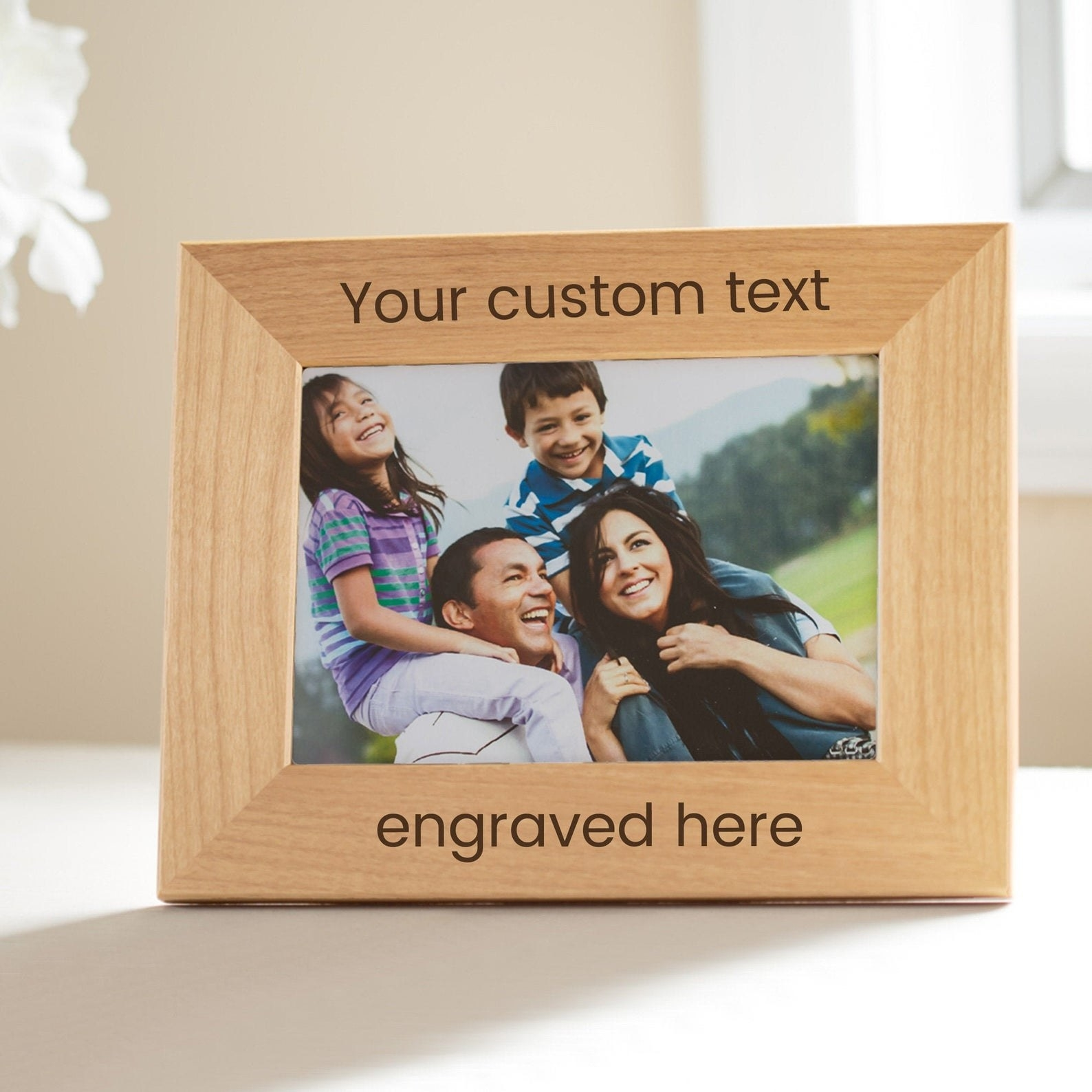 Photo of wood photo frame with text engraved on the top and bottom