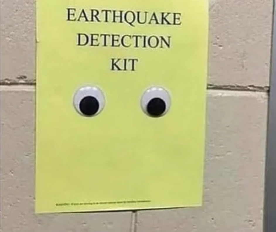 "A paper with googly eyes and ""earthquake detection kit"" written on it is attached to the wall"