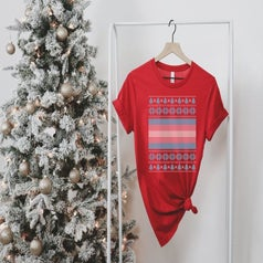 a re t-shirt with a trans* flag in the center and Christmas sweater pattern around the flag