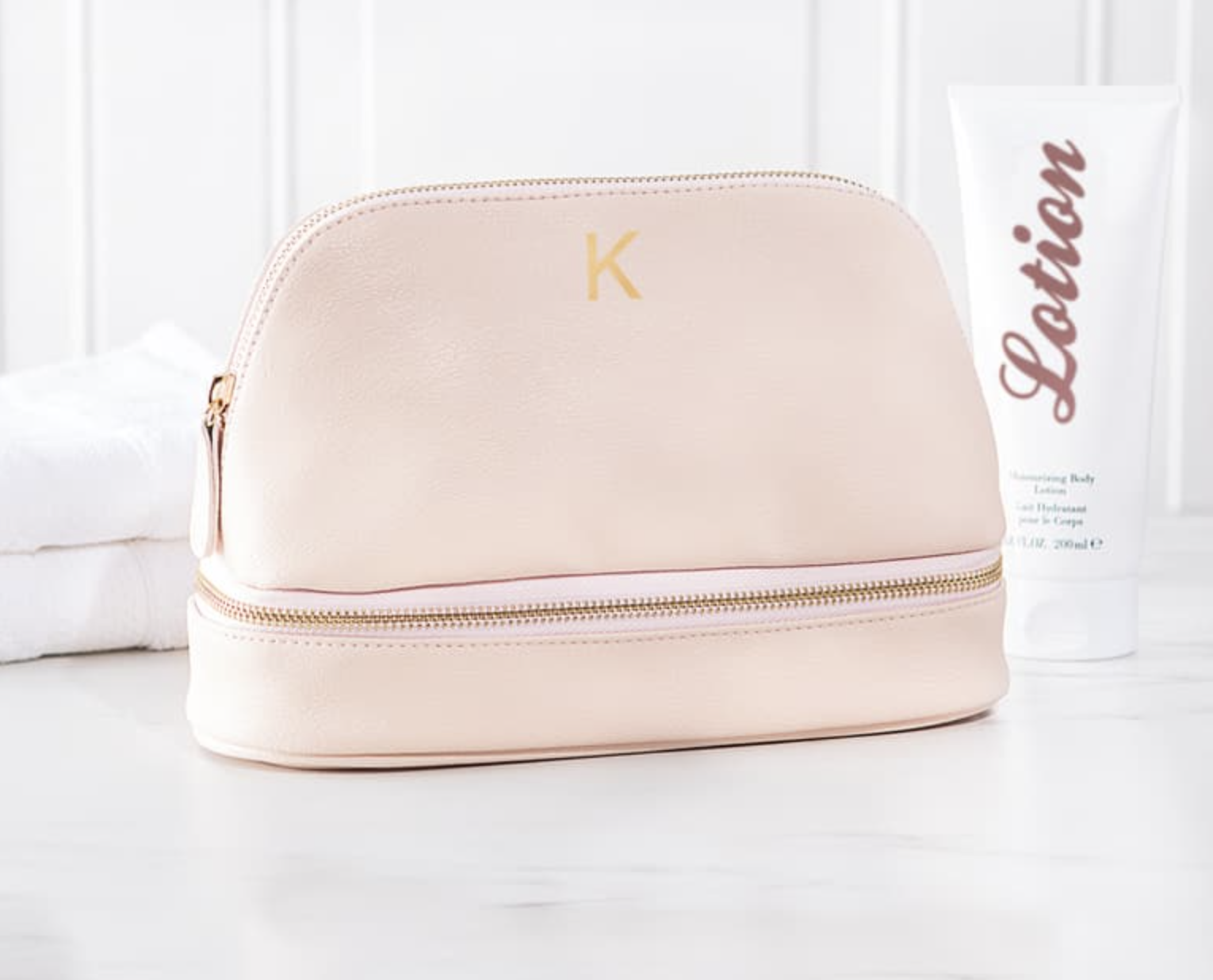 Blush pink cosmetics bag with a gold letter K at the top