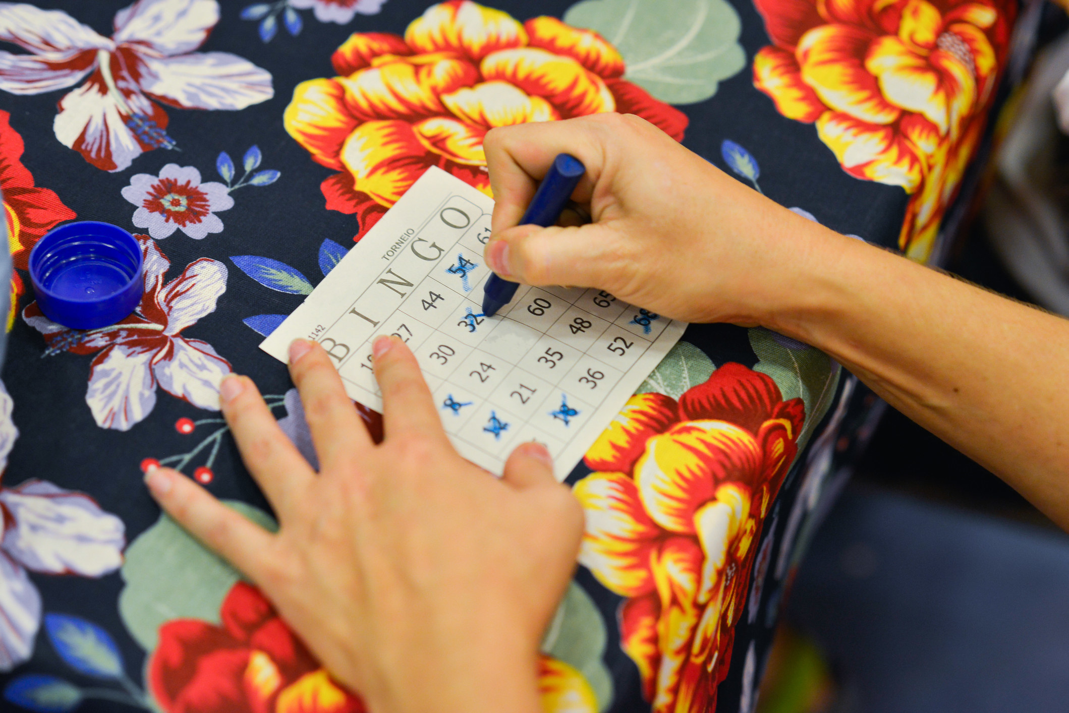 A hand crosses off a number on a Bingo sheet over a floral tablecloth