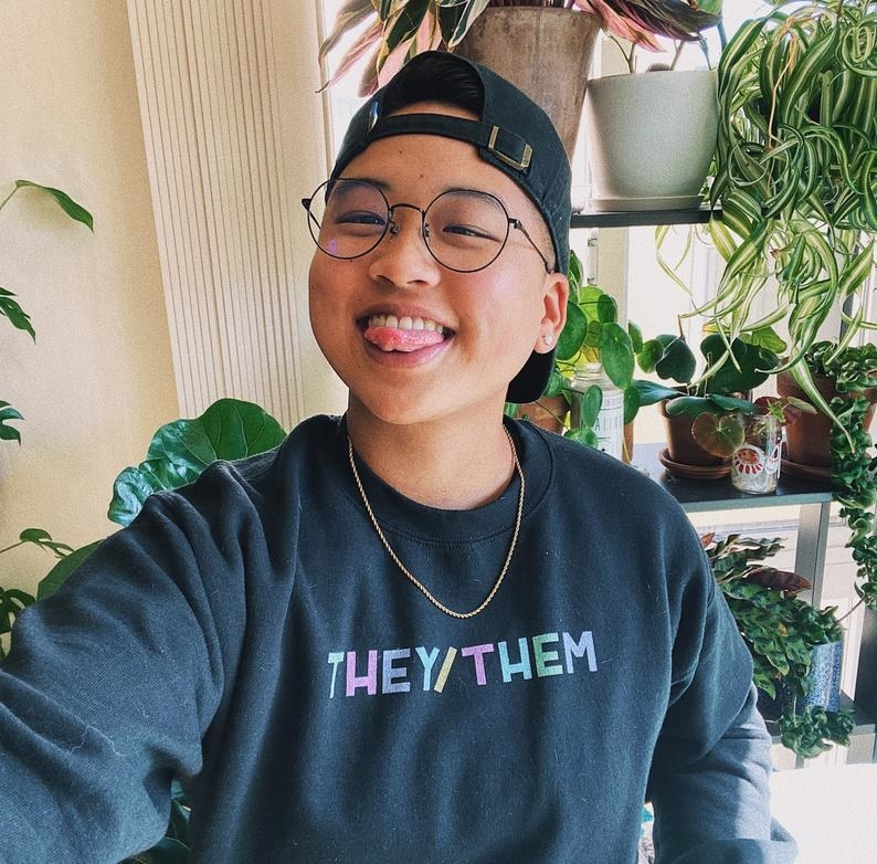 a model wearing the black they/them sweater