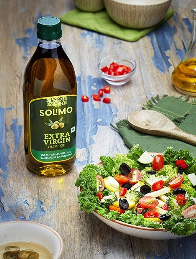 Bottle of olive oil on a wooden table next to a bowl of salad.