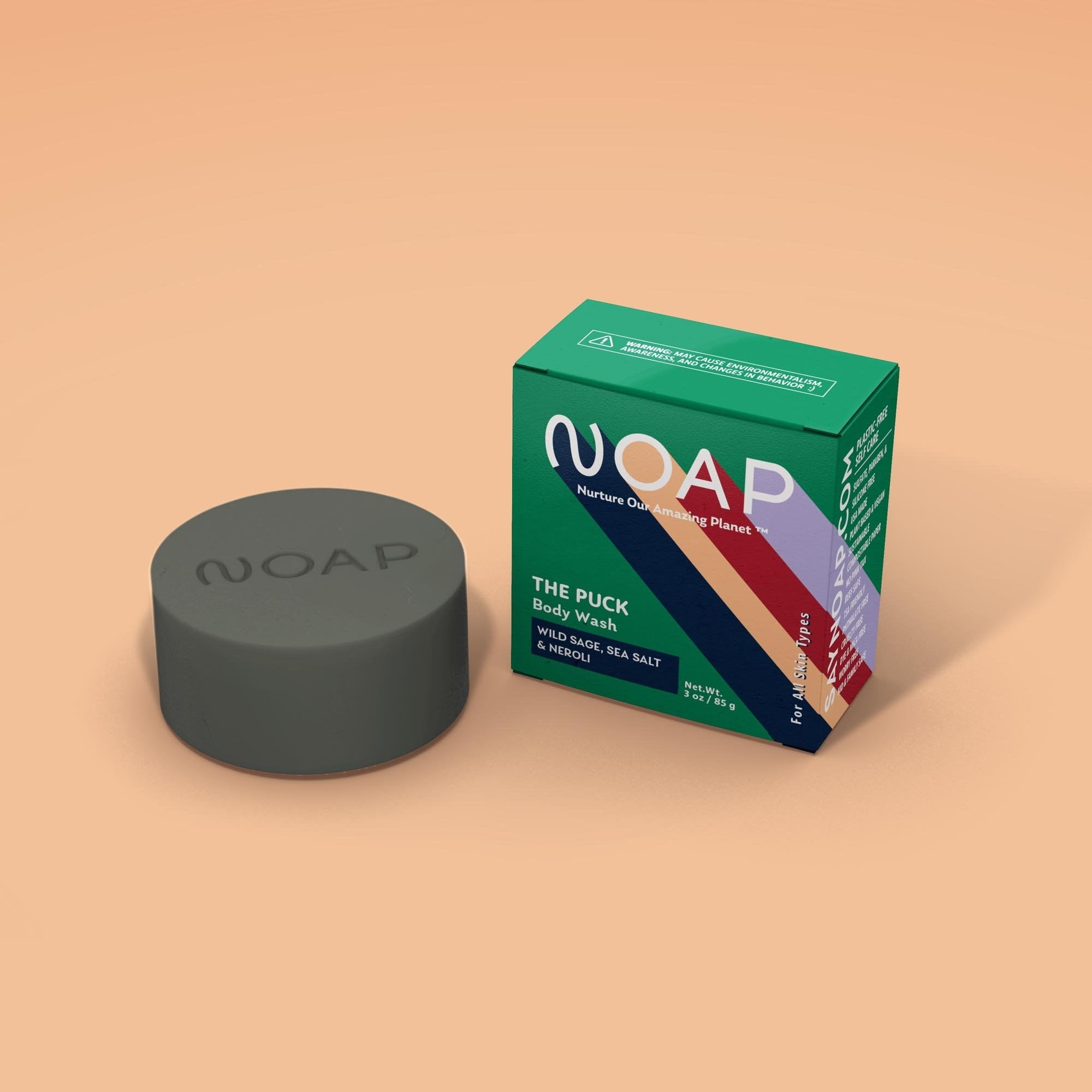 "a puck-like gray bar of soap with ""noap"" etched into it next to a green box with the logo on it"