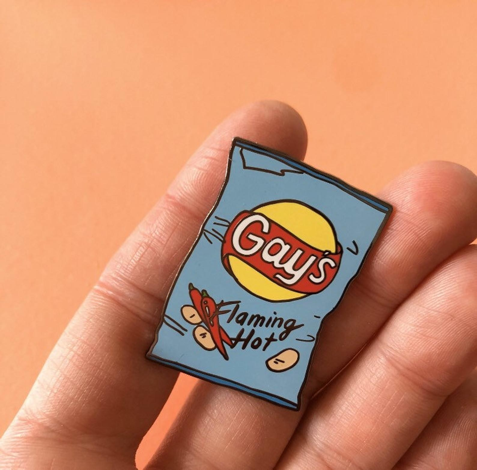 "a small pin shaped like a blue bag of chips with the word ""gays"" on it instead of ""lays"" and flaming hot underneath"