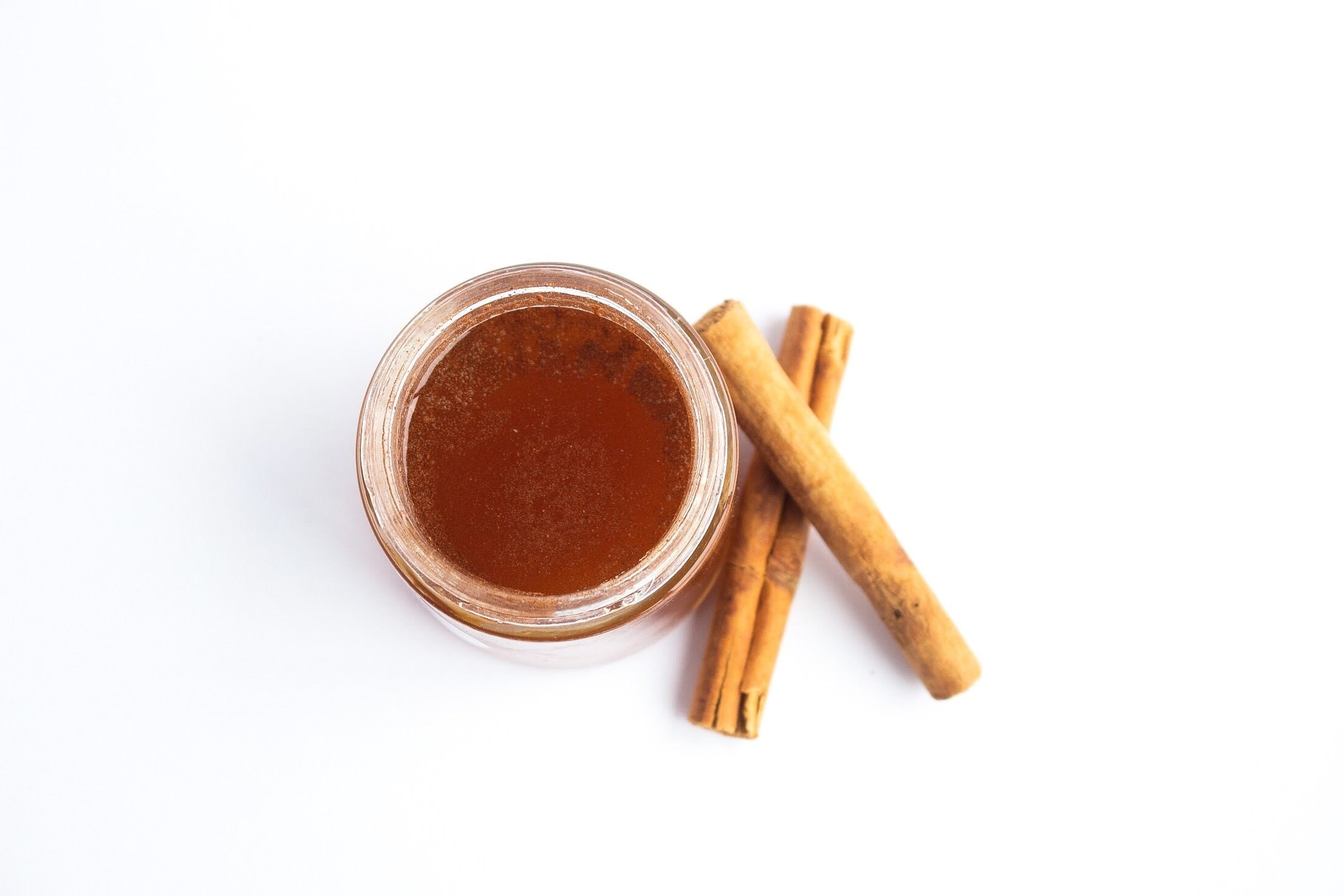 a jar of honey with cinnamon sticks next to it