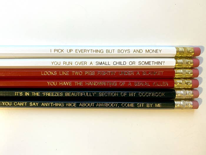 white, red, and black pencils with gold quotes on them