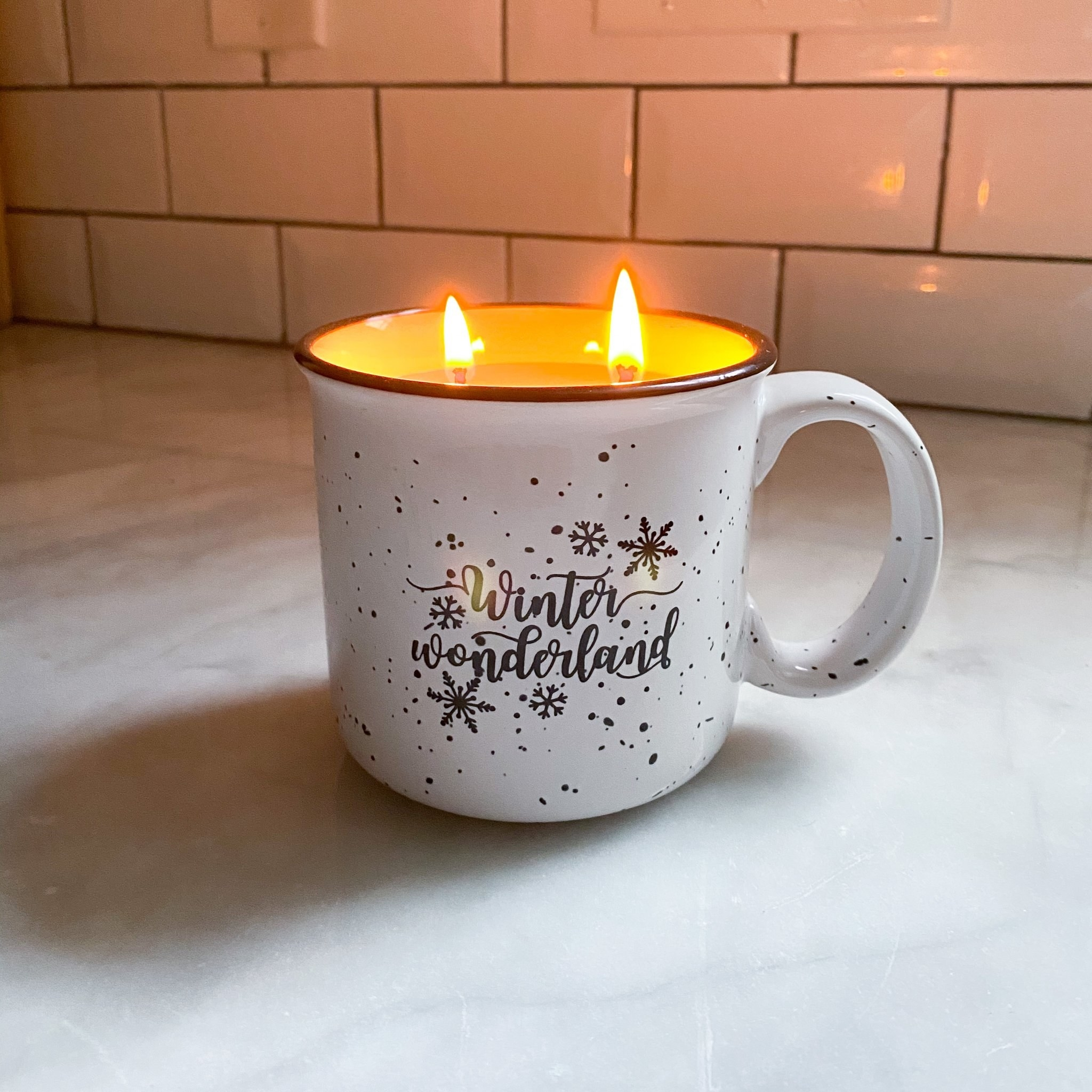 "a white speckled campfire mug that says ""winter wonderland"" on it and has a candle lit inside"