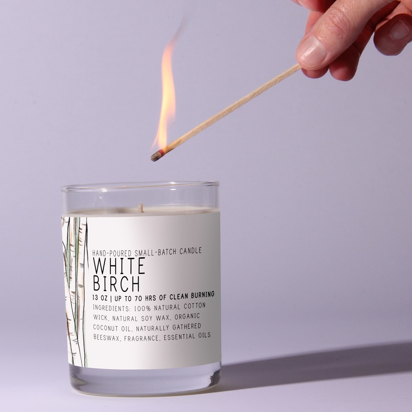 a model lighting a candle with a white label and birch trees on it