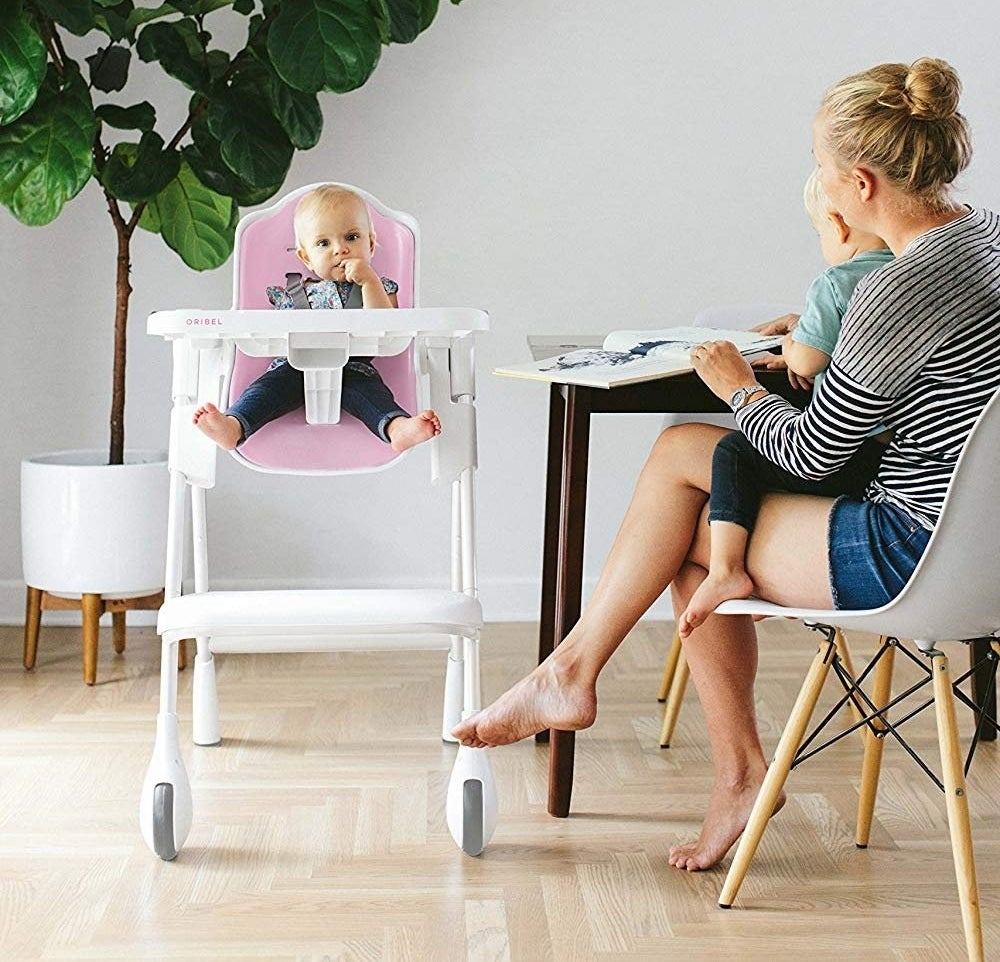 Child model sitting in white baby highchair with pink and gray accents