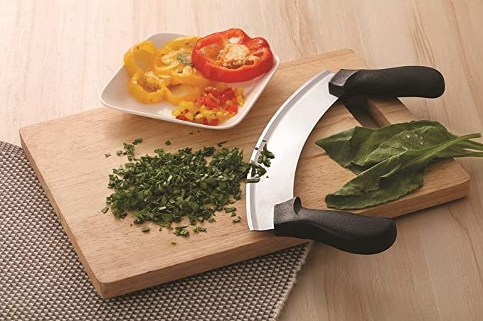 Mezzaluna knife on a cutting board with some chopped herbs on the side.
