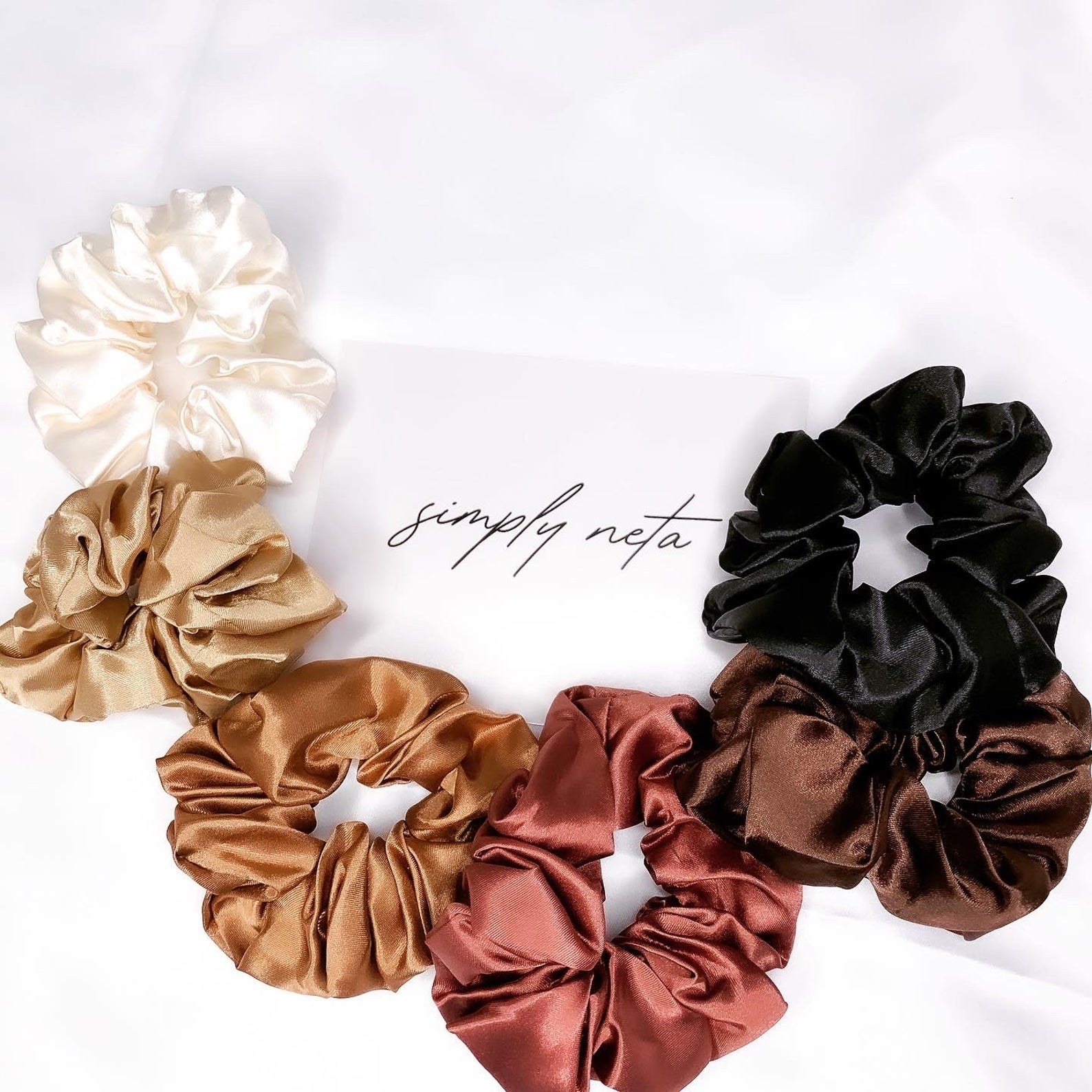 The scrunchies in cream, nude, brown, brick red, and black