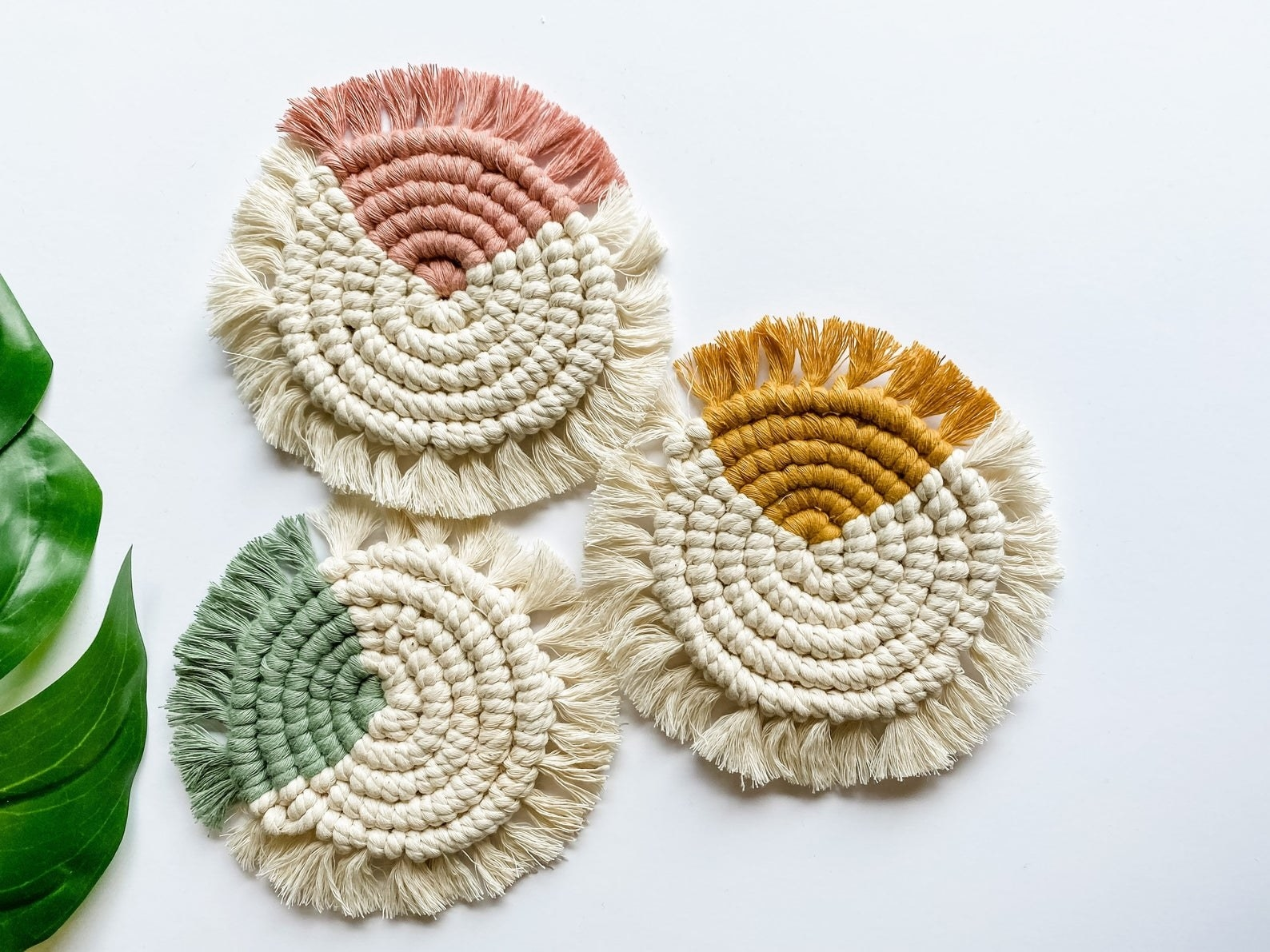Round cream colored macarame coasters with tassels and a small colored portion in yellow, green, and pink