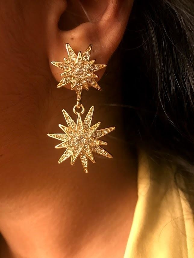 A reviewer wearing the earrings, which are two connected stars filled with white crystals