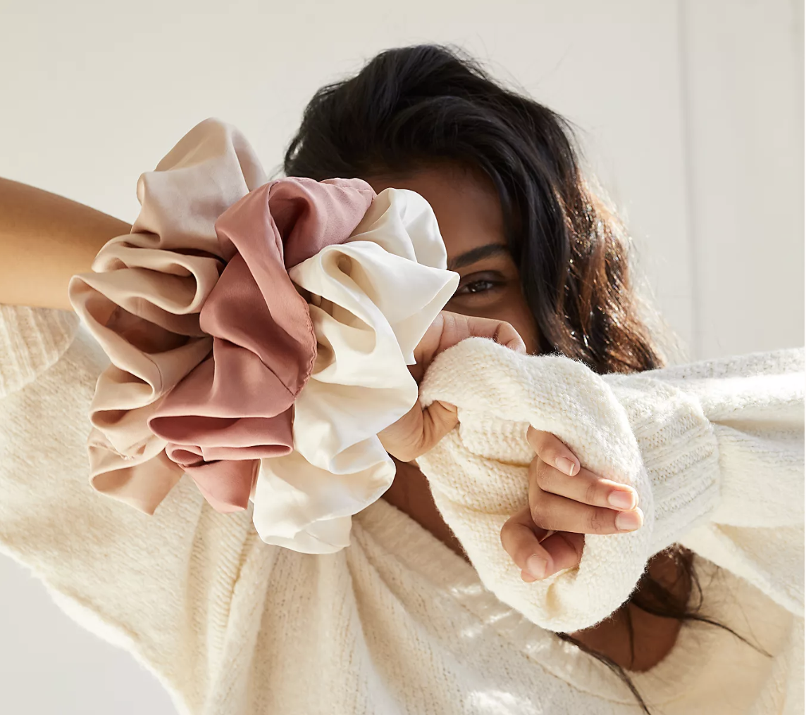 Model with three large silk scrunchies in beige, pink, and white on their wrist