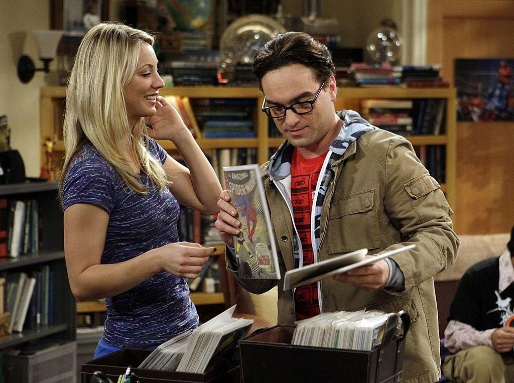 Penny smiling as Leonard looks through comic books