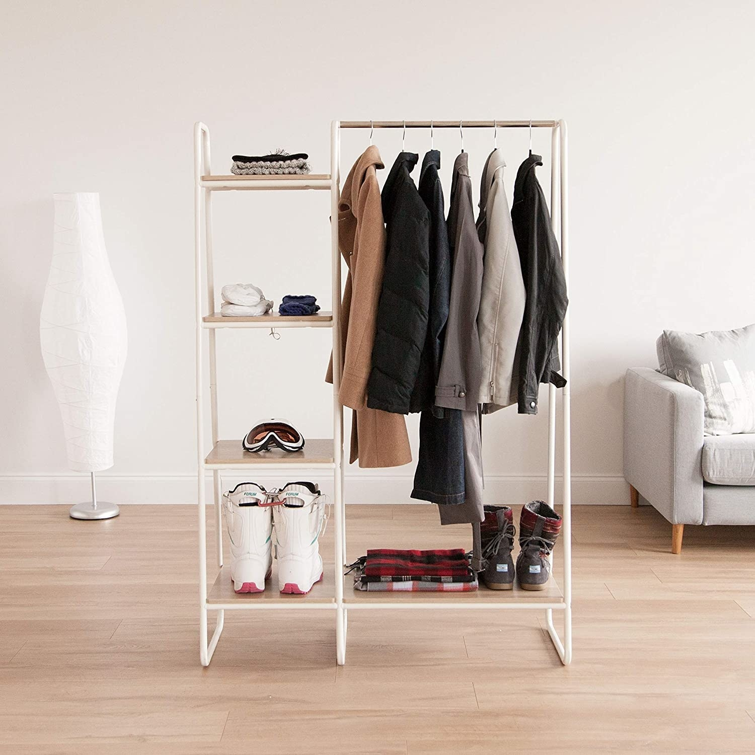 The clothing rack, which also has a three-tier shelf attached to it with shoes and accessories on it