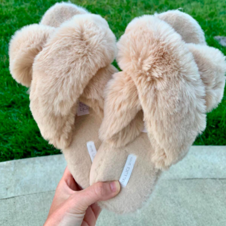 A customer review photo of a person holding the slippers.