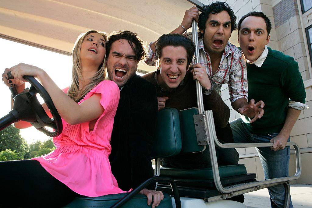 Actors Kaley Cuoco, Johnny Galecki, Simon Helberg, Kumal Nayyar, and Jim Parsons posing in a golf cart