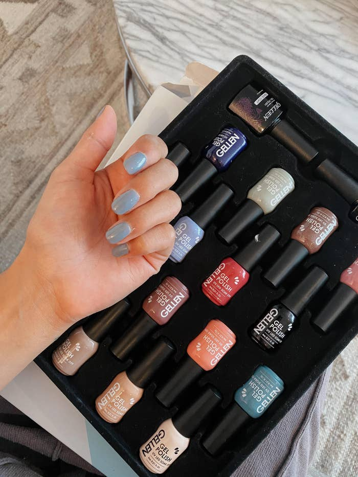 A reviewer photo with their nails painted using the gel nail polish and all of the different nail polish colors in the kit