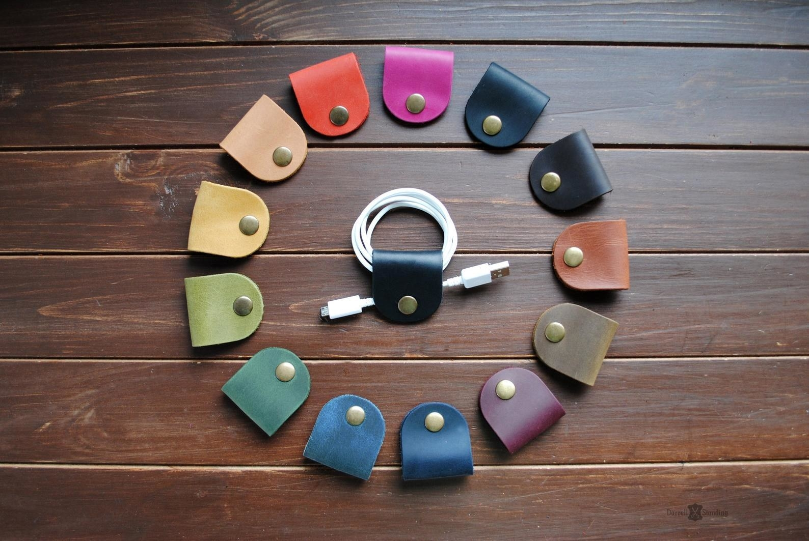 Small leather flaps clasped together by a button and keeping a USB cord from getting tangled