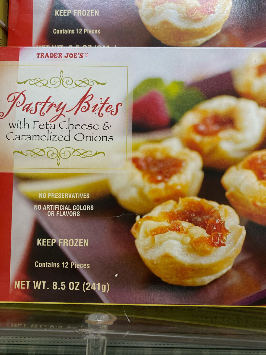 A box of pastry bites with feta and caramelized onions.
