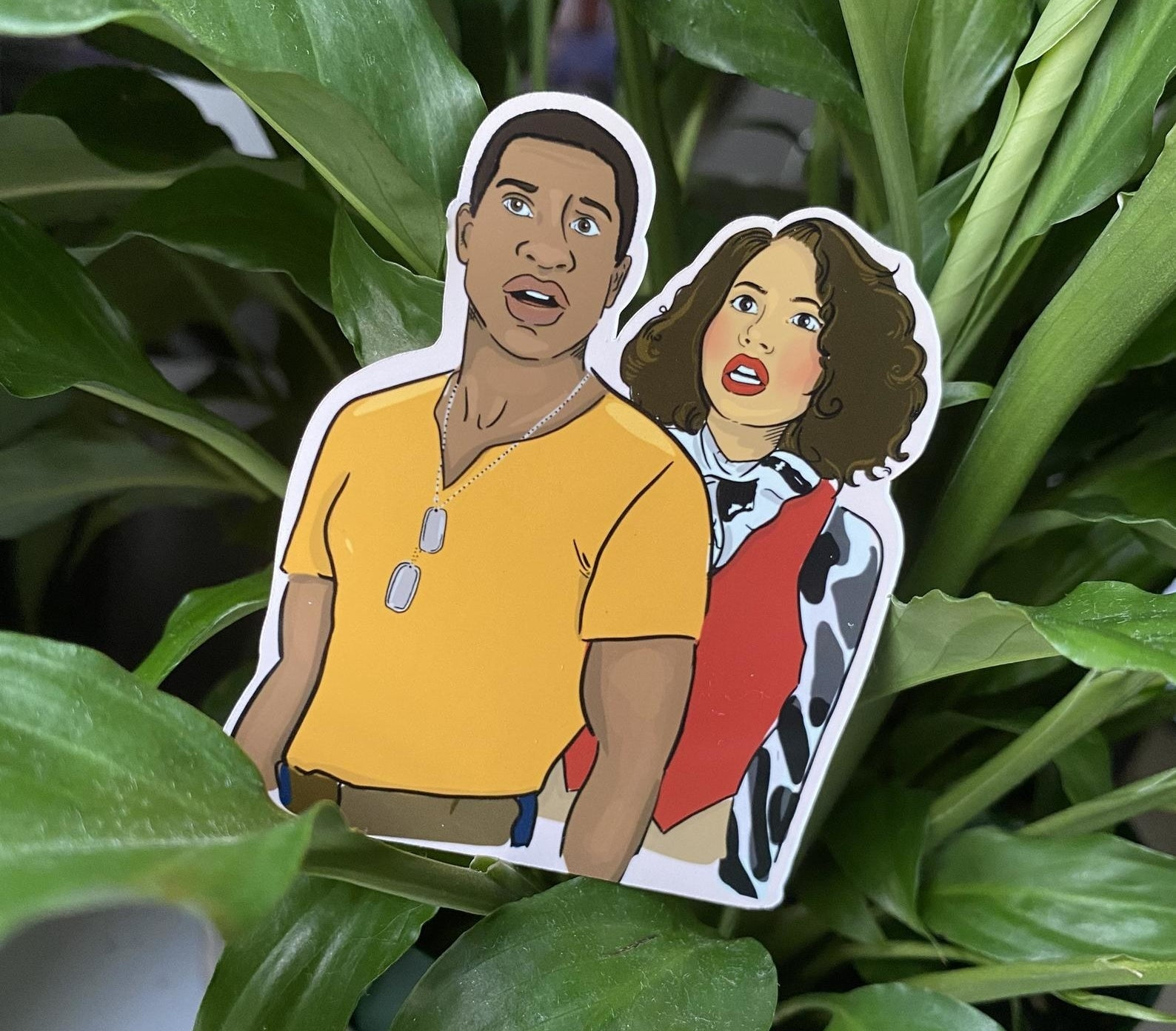 A sticker showing an original illustration of Atticus and Leti from HBO's Lovecraft Country