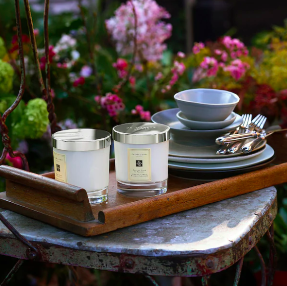 A pair of candles on a wooden tray nestled onto an outdoor bistro table