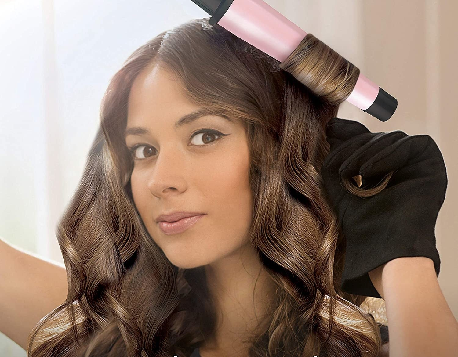 A model using the curling wand to create loose curls in her hair
