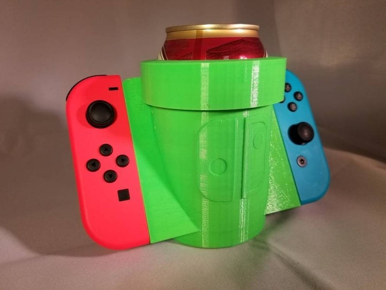 The green cupholder holding a can, with pieces out to the side holding Joy-Cons