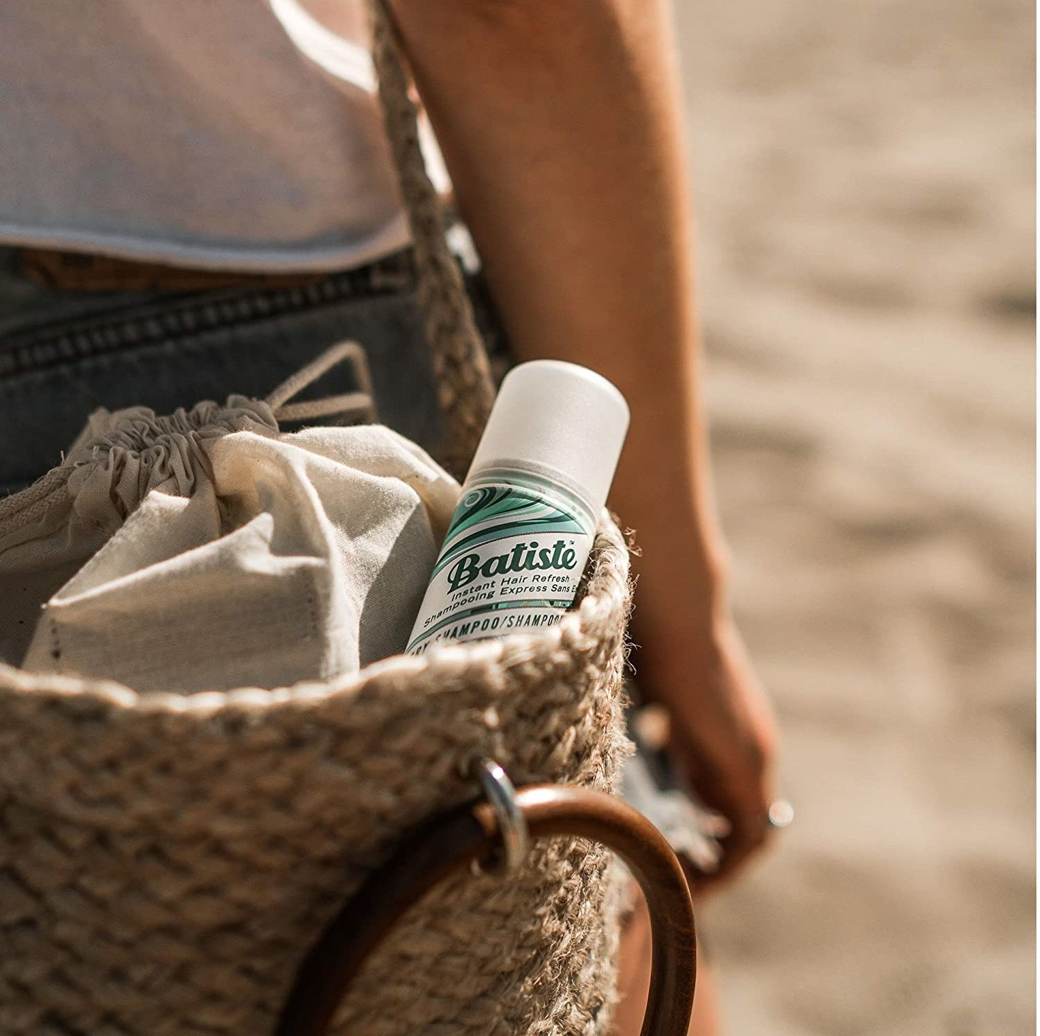A bottle of Batiste dry shampoo poking out of a model's purse