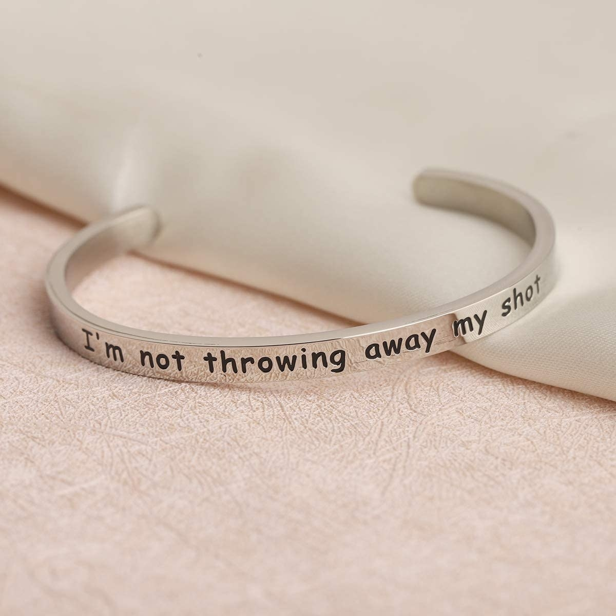 """The silver bracelet printed with """"I'm not throwing away my shot"""""""