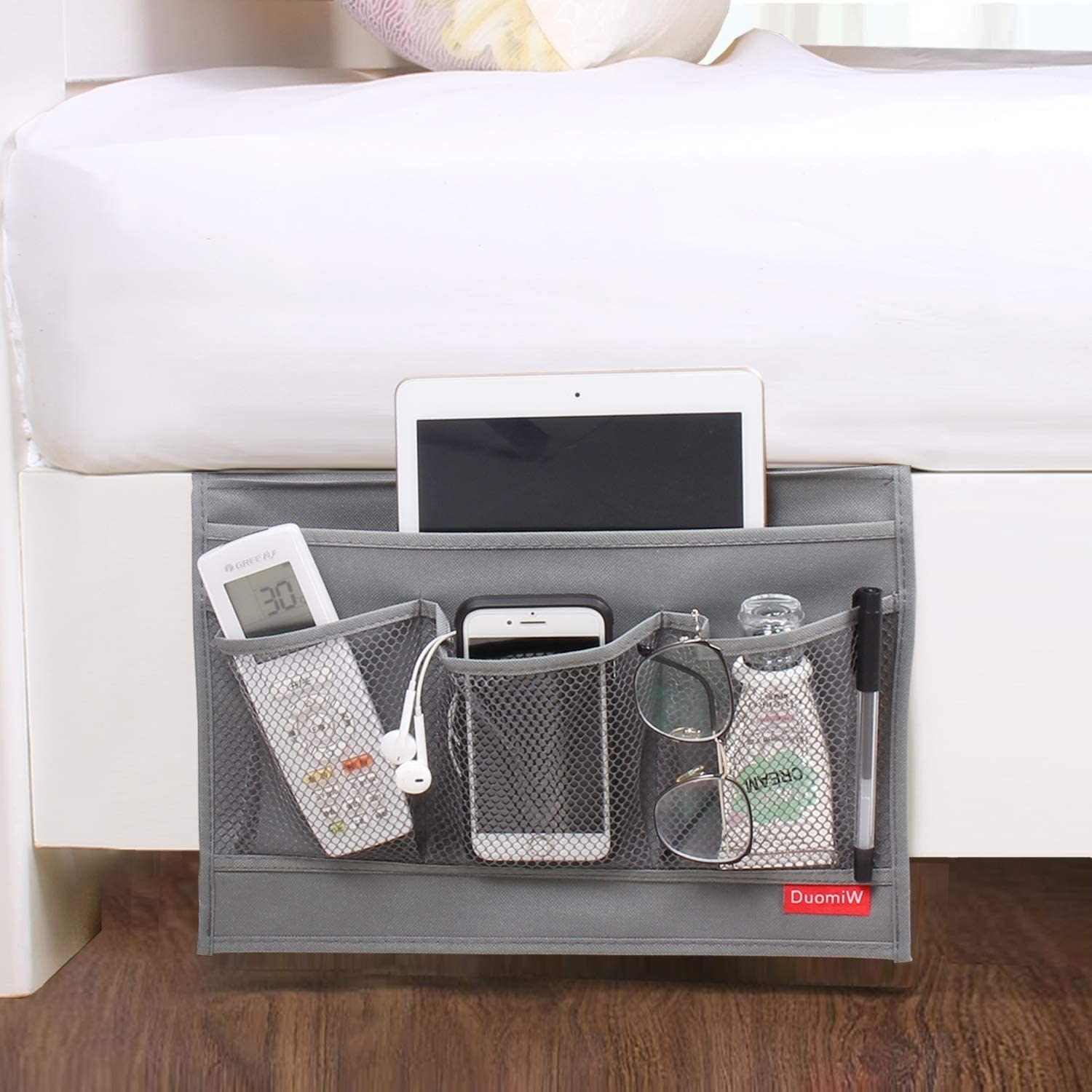 The grey bedside caddy holding a remote, iPad, cellphone, glasses, pen, lotion, and headphones