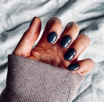 Reviewer with black sparkly nails