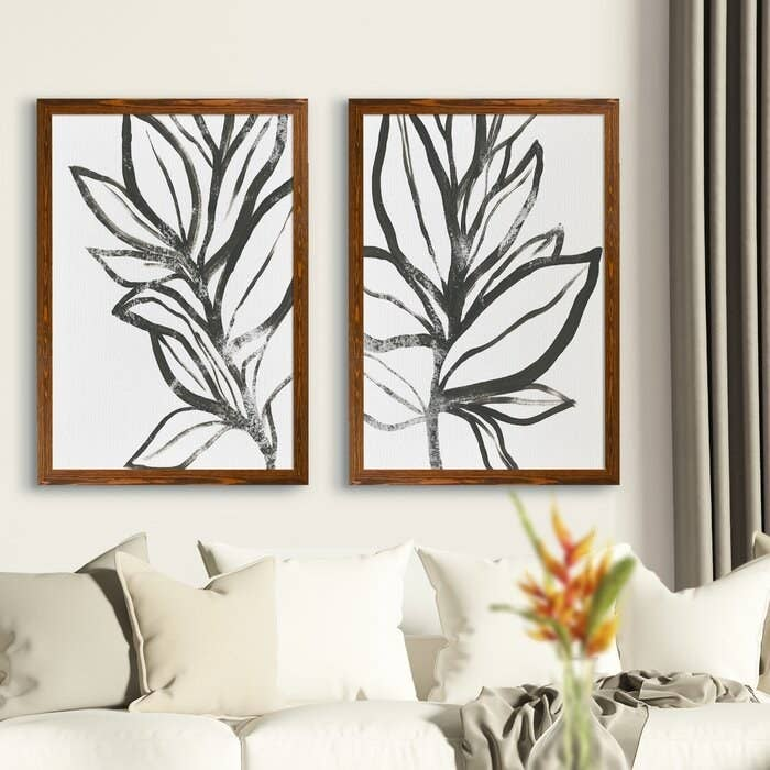 two framed leaf prints hanging over a white couch