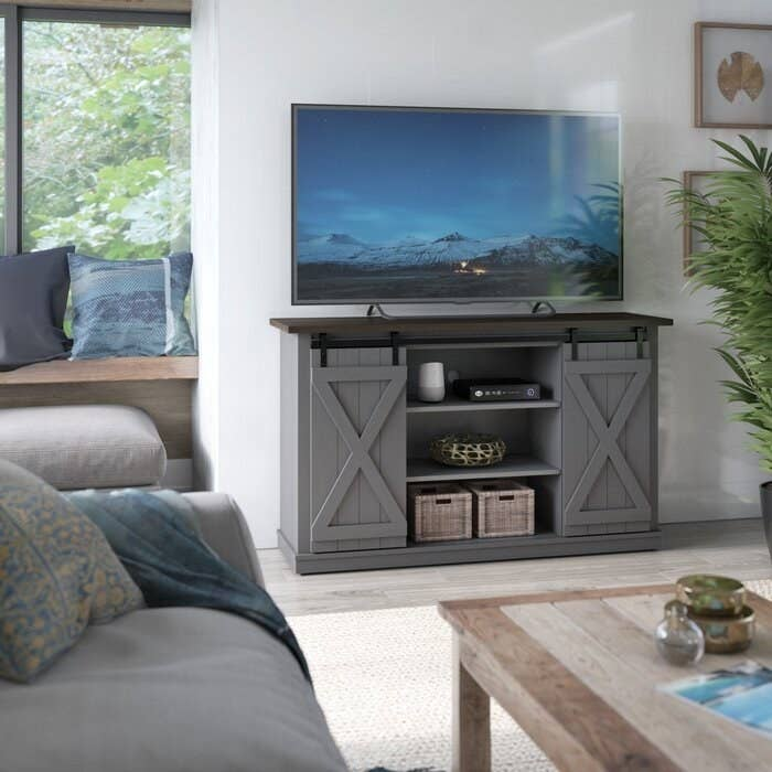 gray tv stand with sliding doors holding up a TV and displaying a vase and basket in the front