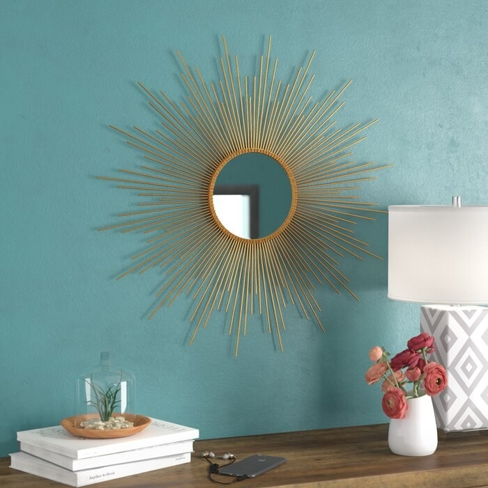 golden accent mirror hanging on a blue wall