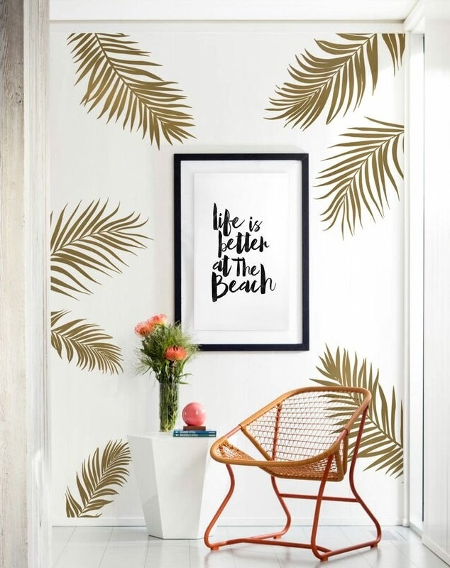 A white wall with seven giant gold palm leave stickers behind a chair and side table