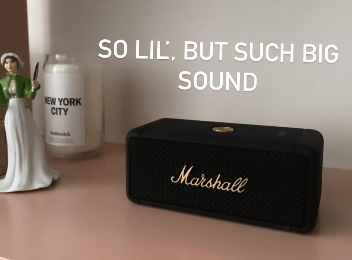 The black rectangular speaker that's shorter than a candle on a bookshelf with gold lettering that says Marshall