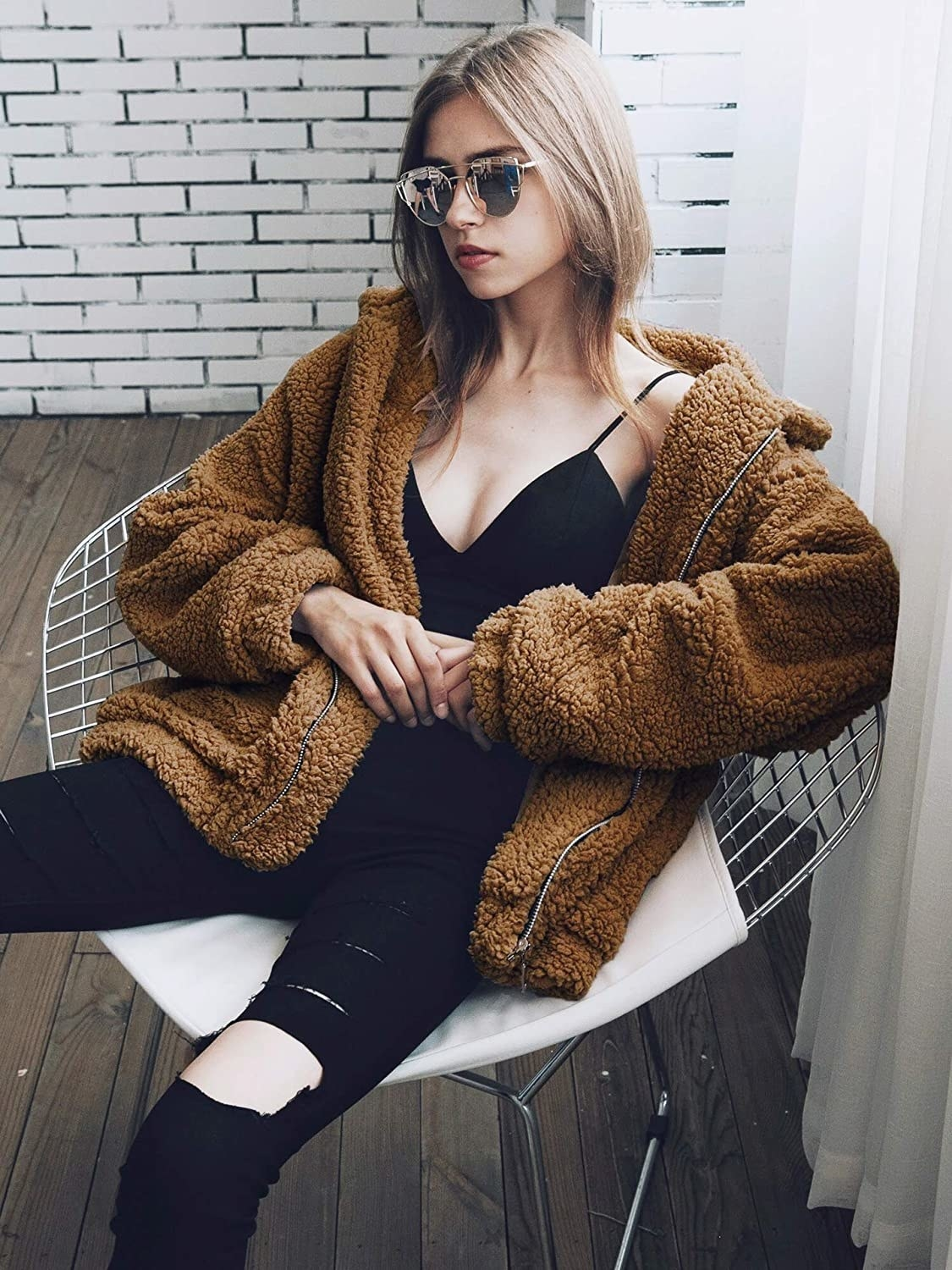 Model wears brown teddy coat with a black crop top and distressed black jeans