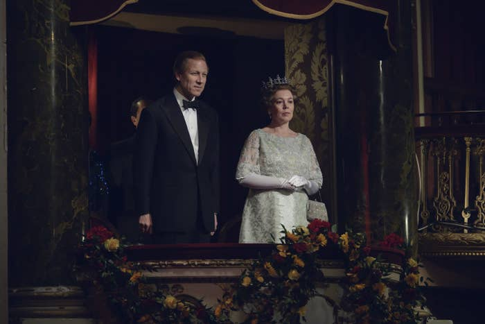 Tobias Menzies as Prince Philip and Olivia Coleman as Queen Elizabeth II standing in a theater balcony