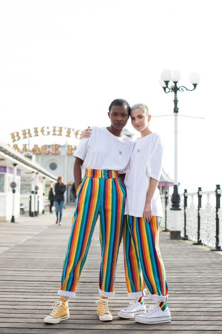 Two models wear the Addison high waisted rainbow jeans on a pier