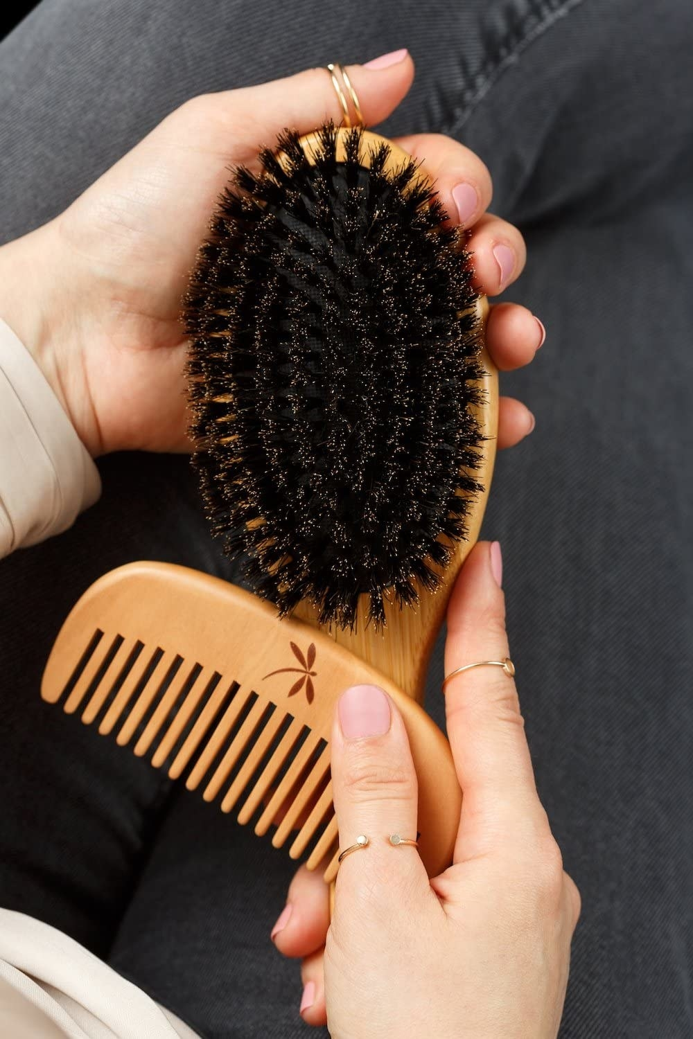 person holding boar bristle brush and wooden comb