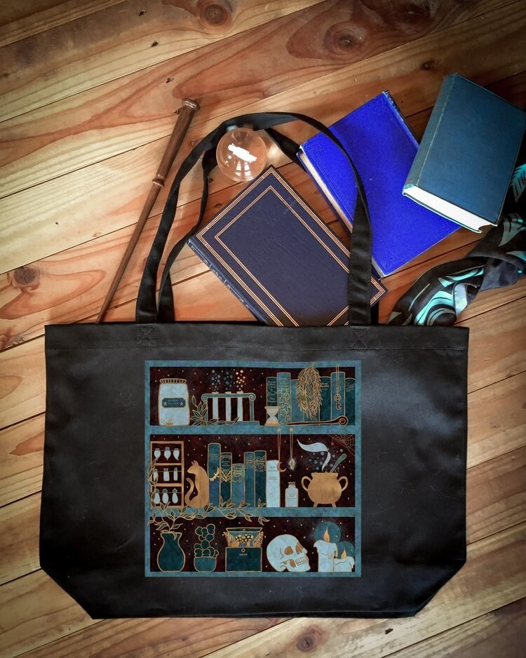 The black tote with an illustration of shelves holding books, a skull, a cauldron, candles, plants, and potions