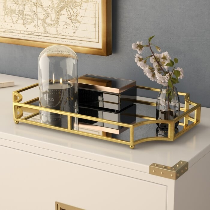 golden decorative tray with a candle vase and jewelry box on