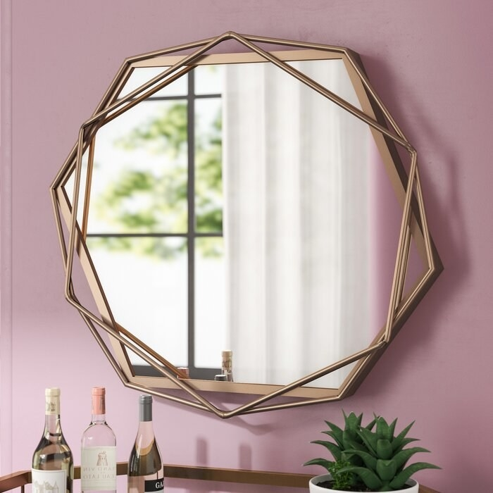 gold accent mirror against a pink mirror